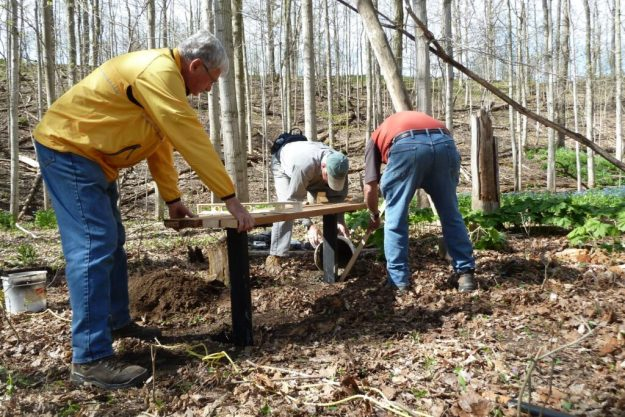 Jim holds the new bench steady while Brian pours cement and Richard spreads it around.