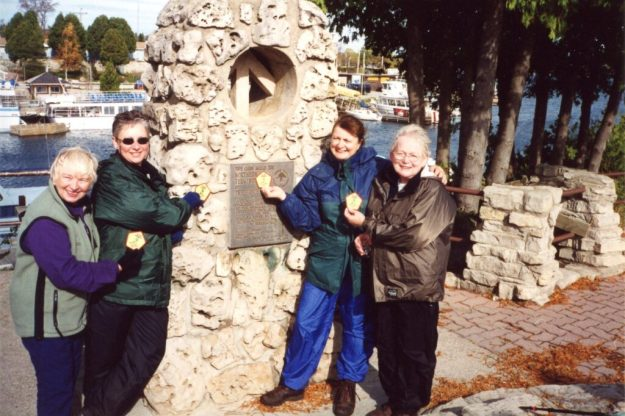 Pat Turow and fellow hikers at end of 900 km hike on Bruce Trail in front of Northern Cairn in Tobermory showing special badges made for the unique hike.