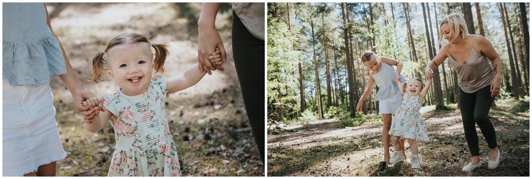 Barn som hoppar mellan mamma och syster på familjefotograferingen i Tullinge
