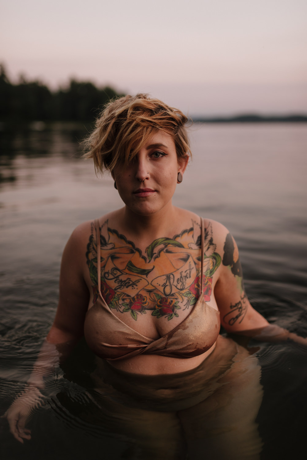 Woman with tattoos standing in water during sunset.