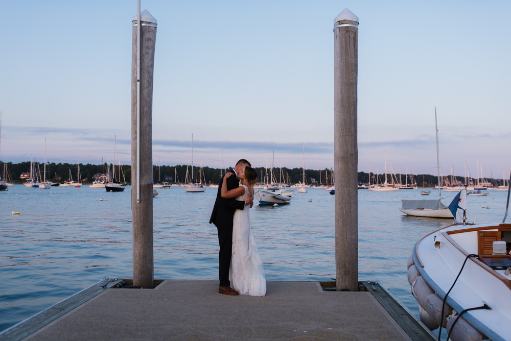 Wedding couple standing on dock by the water kissing.