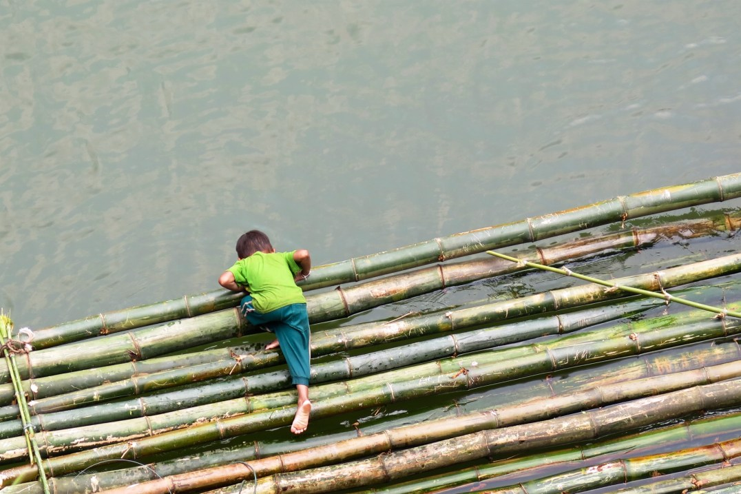 Un enfant aidant à la construction de radeaux en bambou pour Pimai