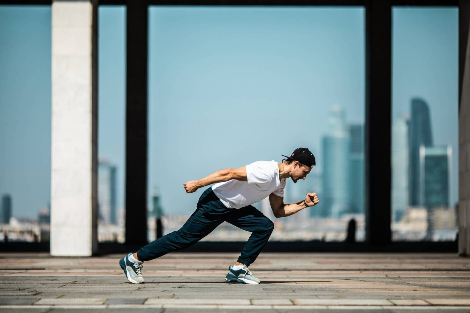 man in white t shirt and black pants in a running position