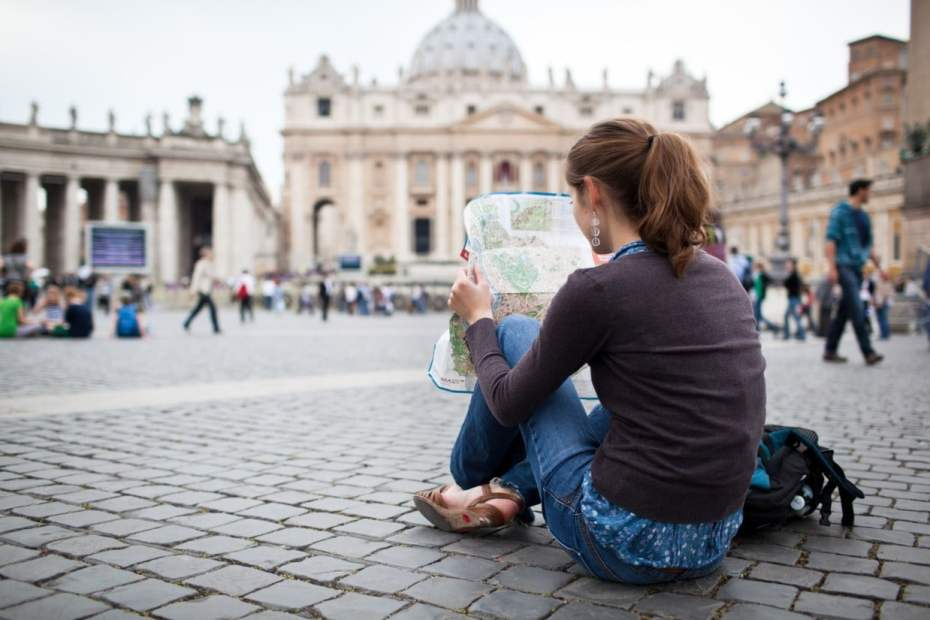 Credits by lightpoet, Pretty young female tourist studying a map in Italy