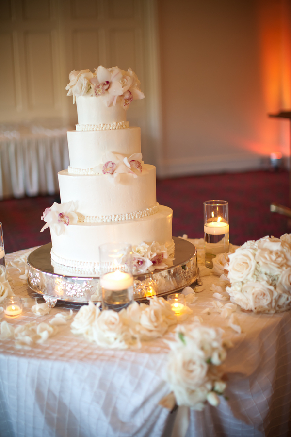 White Wedding Cake With Flowers On Silver Stand
