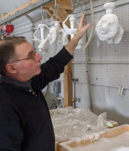 Caster inspecting a row of door knockers dipped in ceramic slip and sand to create the shell for casting.