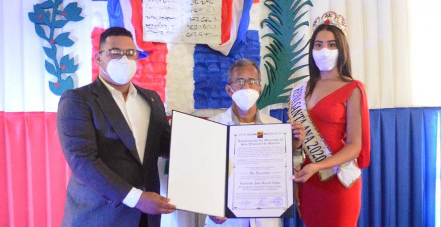 El locutor José Manuel Acosta, recibe su reconocimiento de manos del regidor Anthony Acevedo y la Reina Santa Ana 2020.