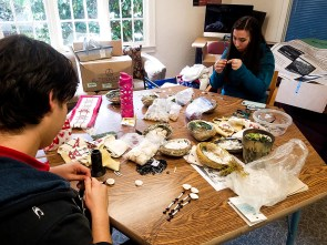 Students Adrian Romo, on the left, and Elaine Tseng-Gill, on the right, beading their designs for the accents that will go on the sashes. Photo by Sinhai Dorantes