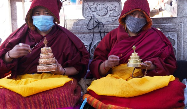 Lhasa: nuns making a mandala offering in front of the Jokhang Temple