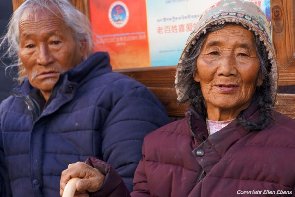 Lhasa, elderly couple resting on a bench at Barkhor Street