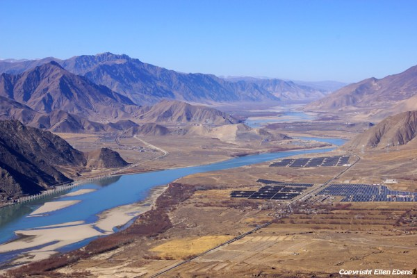 View from the road climbing to Densatil Monastery on the Yarlung Tsangpo Valley, You can see the modernisation of Tibet on this picture clearly, Solar power fields on the right side of the river and on the left the building of the railroad from Lhasa to Chengdu.