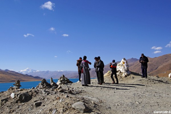 Pilgrims at Yamdrok Tso Lake with on the background the big snow mountain Nojin Kangtsang