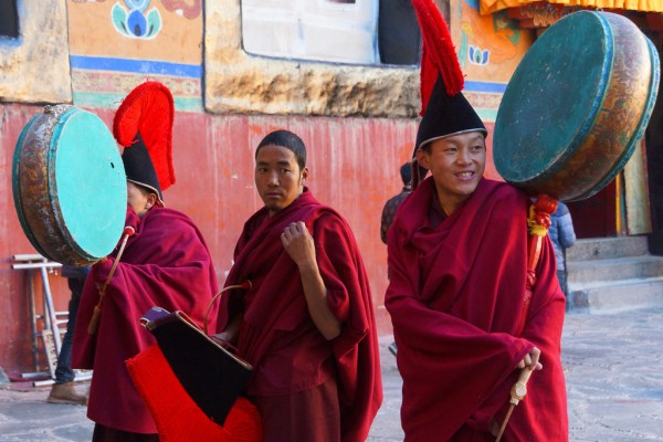 The monks with the music instruments are getting ready for the dancing