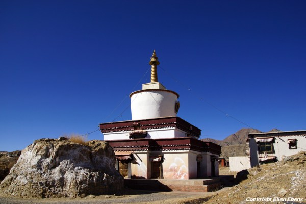 The ruins of a destroyed stupa and a new stupa at Narthang Monastery