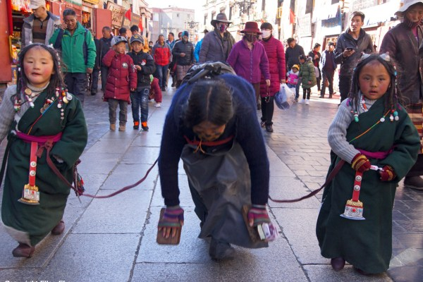 Lhasa: a mother with to little daughters prostrating at the Barkhor