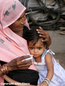 A young girl clings to her grandmother
