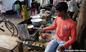 Young boy cooking milk tea at a street restaurant