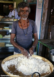 A man at a street restaurant prepares food