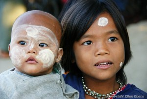Young girl with her baby brother at the river, Monywa