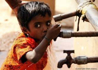 Little girl drinking water from the tap in Badami