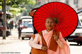 Yangon, a nun with a traditional paper umbrella against the sun