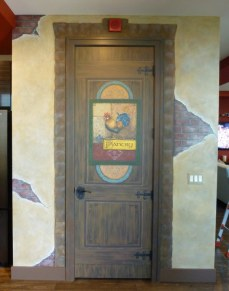 Pantry Door painted to look like old wood with old wrought iron hardware, beautiful signage with a rooster. Walls painted to look like old stucco, cracked and broken away to reveal bricks. Stone surround on the doorframe. Mural by Ellen Leigh