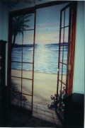 Hawaiian Doors Bypass closet doors painted with a view of the beach at sunset, footprints in the sand. Mural by Ellen Leigh