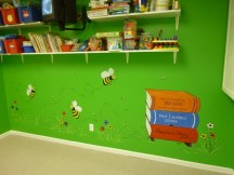 Spelling Bees. Cartoonish bees and a hive made out of books in the library at the day care. Mural by Ellen Leigh