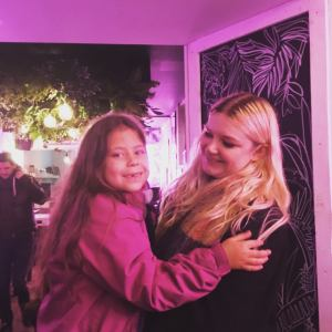 Image Description: Ellie (blonde woman in her late twenties) smiles as she is lifting up and cuddling a young girl, who is smiling with a little tooth gap, is mixed race and has long wavy brown hair and a bright pink coat. The lighting has a pink tinge, as we are inside a local cafe and there is a lot of fake greenery in the background.