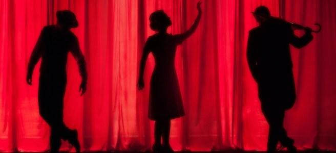 Silhouettes on stage in front of red curtain