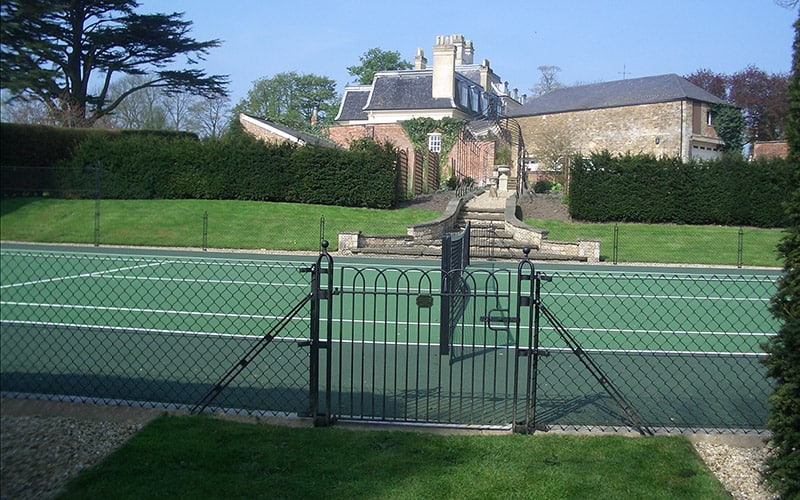 Stylish obelisk fencing frames the tennis court