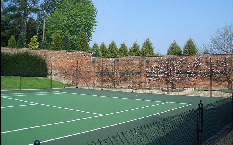 Flint wall tennis court fence with a flint wall by Elliott Courts - EnTC.