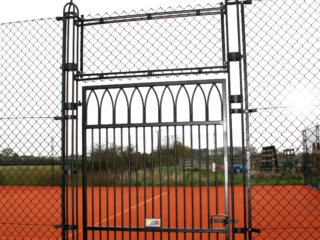 Gothic tennis court gate with unique design and obelisk supports