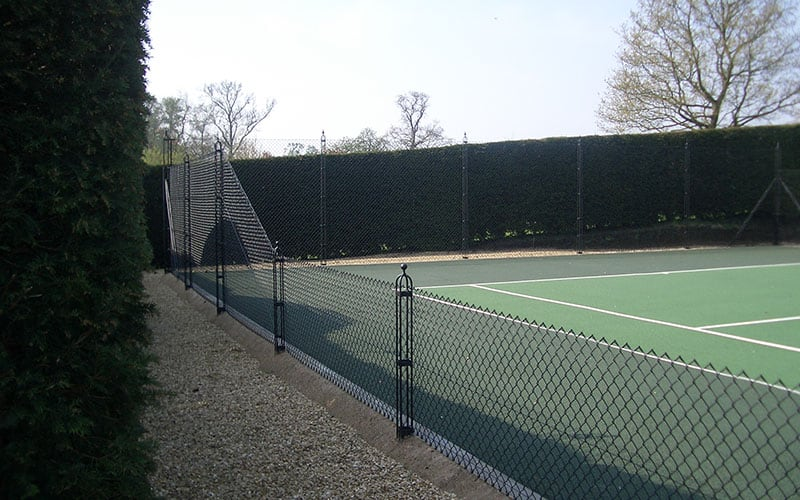 Obelisk tennis court fencing framed by a mature hedge