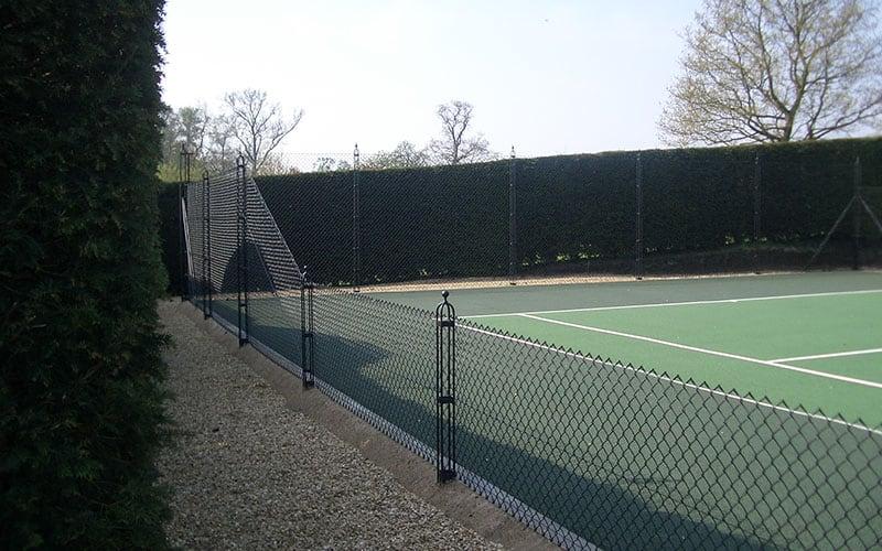 Obelisk tennis court fencing framed by a mature hedge