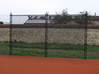 A double sized practice wall is part of the tennis court fence…