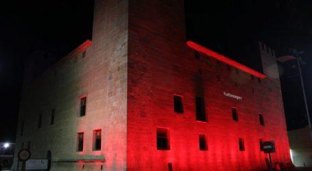 El Castell d'Alaquàs s'ilumina de roig recolzant la cutura segura