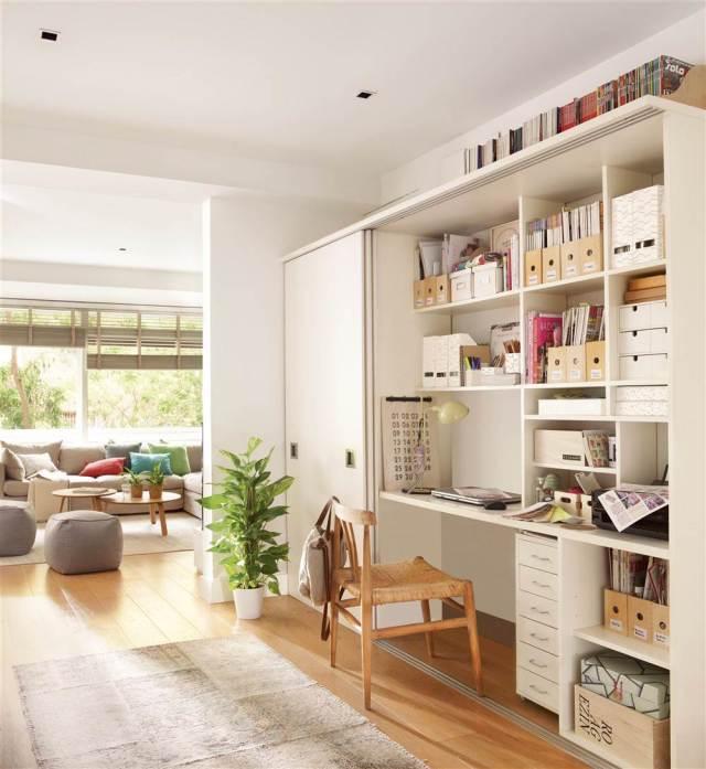 Estudio con mueble con escritorio, estanterías y armario integrados en blanco, silla de madera y fibra, cajas, archivadores, libros y con el salón al fondo con pufs y mesitas auxi