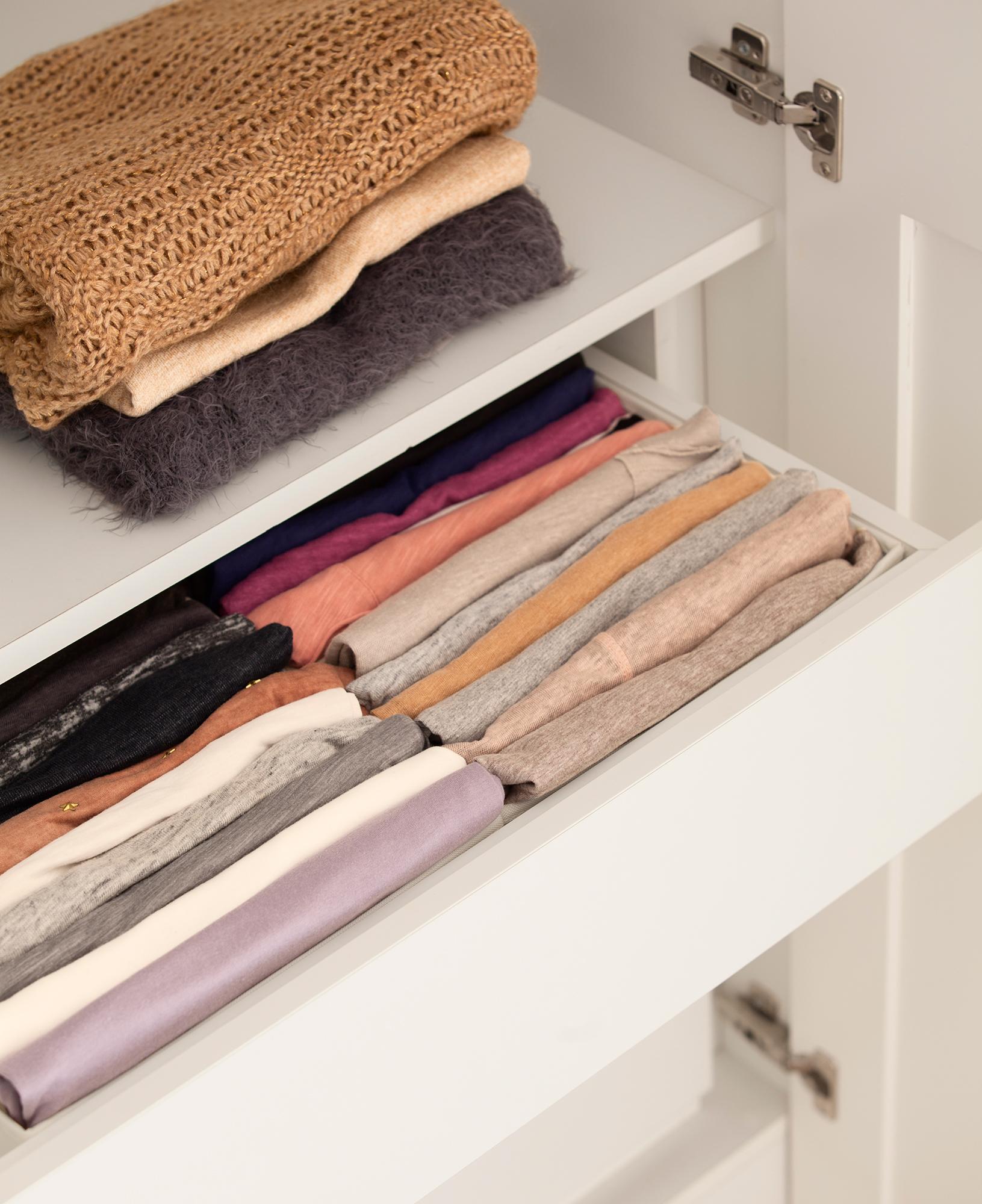 Detalle de cajón de armario abierto con camisetas ordenadas con el método Konmari