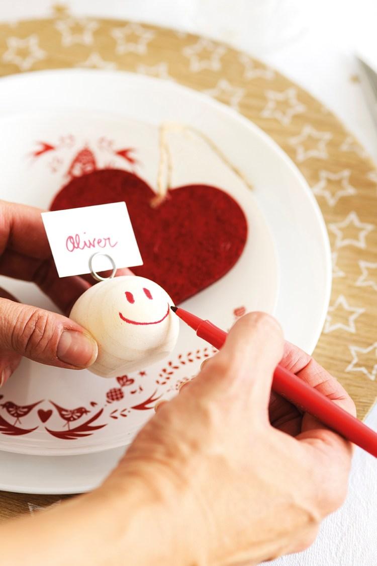 00444897. Detalle de una mano pintando un portanombres para la mesa del comedor_00444897