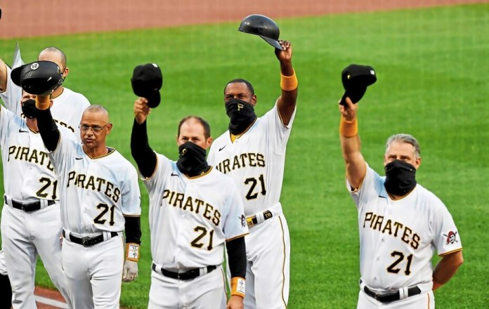 Members of the Pittsburgh Pirates, including former player and coach Joey Cora (before left), greet the crowd after the Roberto Clemente ceremony at PNC Park in Pittsburgh.