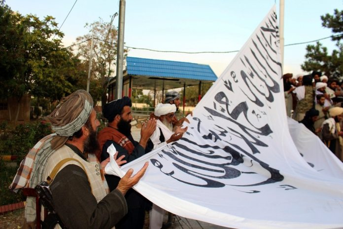 Members of the Taliban raise their flag in a province of Afghanistan.