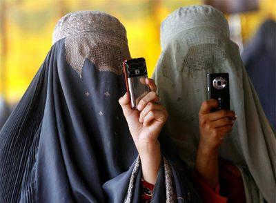 Dos mujeres ataviadas con burka toman fotos durante un mitin en Kandahar (Fuente: diario El País de España)