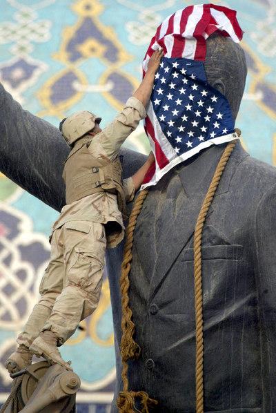 Un soldado coloca la bandera de EE UU sobre la estatua de Sadam Husein