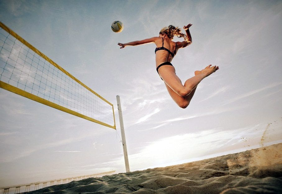 blog picture of lady playing beach volleyball jumping high for a spike