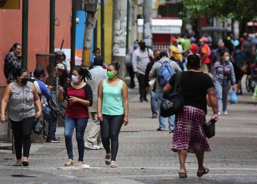 Mujeres con tapabocas caminan este miércoles en la Calle Peatonal de Tegucigalpa (Honduras). EFE/Gustavo Amador