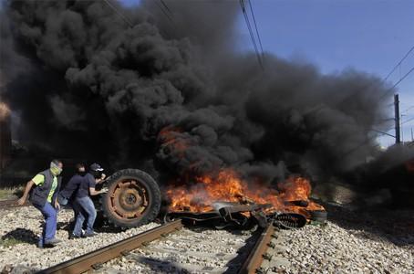 Un grupo de mineros empujan una rueda de camión hacia la barricada incendiada que corta la vía en Bembibre.