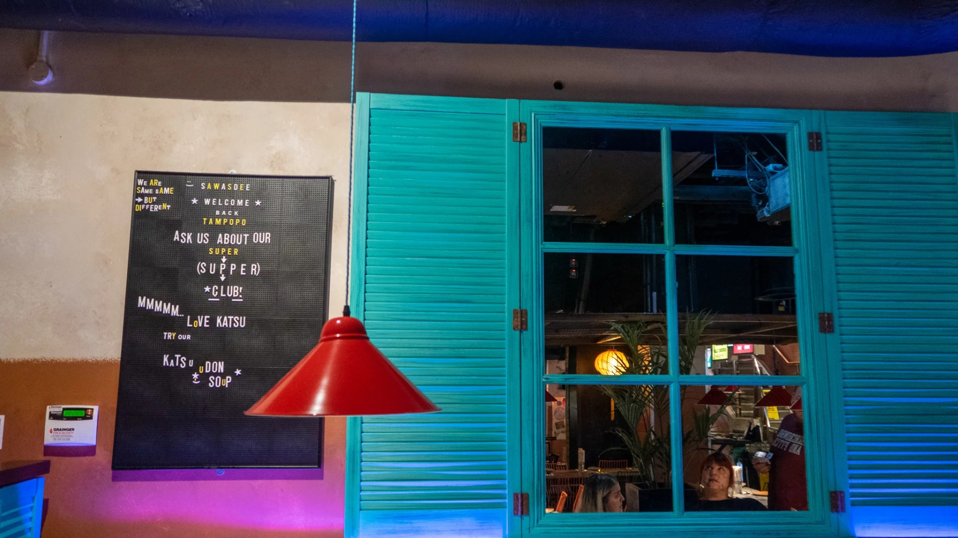 """Tampopo walls with a pin board in the background suggesting the katsu udon soup as well as their supperclub. Fake shutters with a mirror in the """"window"""" pane."""