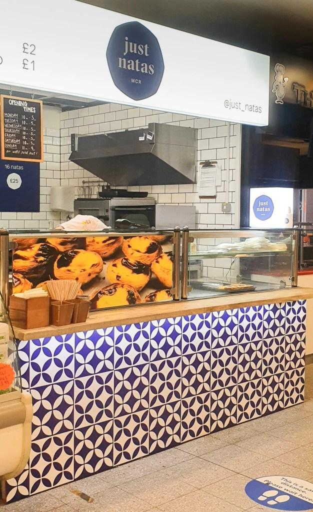 The counter of Just Natas at the Arndale Market. A tray of Portuguese tarts can be seen from the window on the counter.