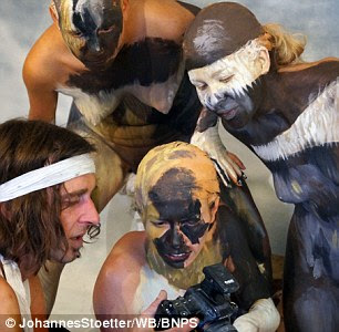 Bodypainter transforms three naked women into a howling Wolf 9